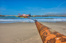 Rusty Pipe Leading Out To The Harbor Dredge.
