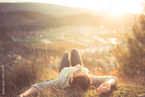 Valokuva  arefree happy woman lying on green grass meadow on top of mountain edge cliff enjoying sun on her face