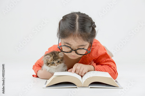 Little Asian girl reading a book with lovely Persian kitten on isolated Canvas Print