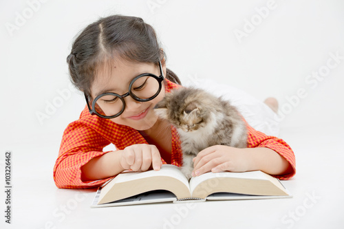 Poster  Little Asian girl reading a book with lovely Persian kitten on isolated