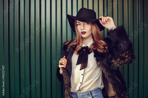 Fotografie, Tablou  Street closeup portrait of a young beautiful lady wearing stylish black fur coat and wide-brimmed hat