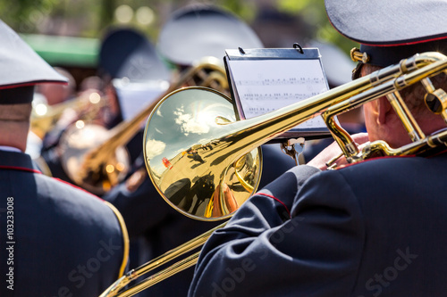 obraz PCV musician of the military orchestra playing on gold trombone