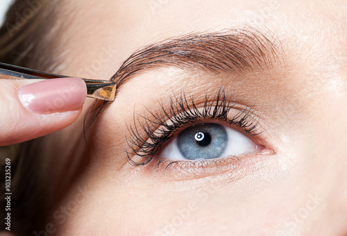 Fotografía  Closeup of a woman pulls out her eyebrows with tweezers