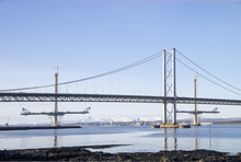 The South Queensferry End Of The Forth Road Bridge, With Two Partially-completed Towers And Deck Of The New Queensferry Crossing In The Background