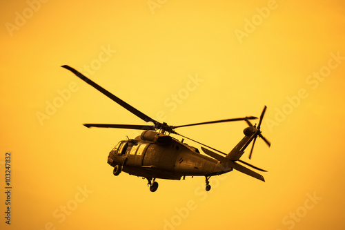 Fotografering  Silhouette of the military helicopter  moving into sky at sunset