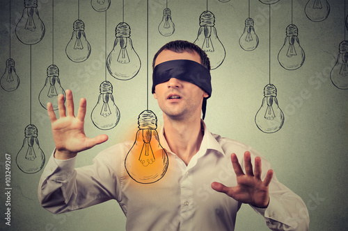 Fotografia  Blindfolded young man walking through light bulbs searching for bright idea