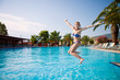 Joyful girl jumping in the pool on holiday