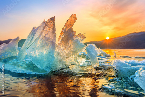 Photo  Very large and beautiful chunk of Ice at Sunrise in winter.