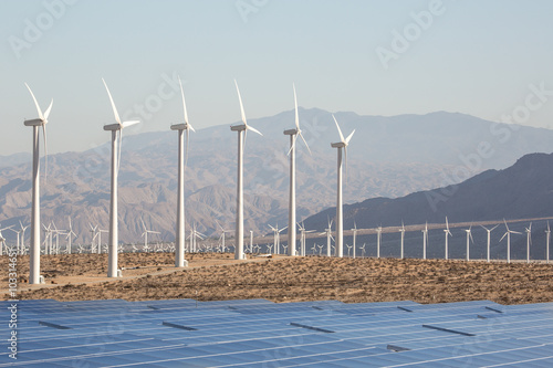 Solar Energy Windmills and Solar Panels in California. Solar panels energy in a California desert with mountains in the background. Sunlight, solar panels and wind turbines.