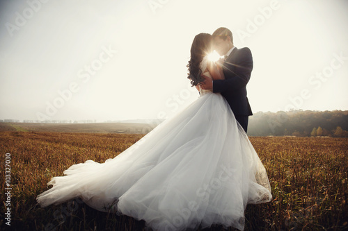 Photo Romantic fairytale newlywed couple hug & kiss in field at sunset
