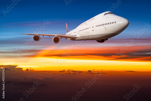 Fototapeta Airplane in the sky at sunrise obraz na płótnie