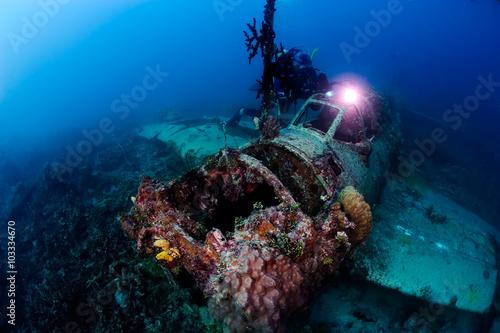 In de dag Duiken Scuba diver exploring wreck plane in the deep.