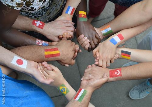 Fotografía  Internationale Brüder und Schwestern mit Flaggen unterschiedlichen auf ihren Armen gemalt stehen miteinander im Kreis und die sich halten Hände