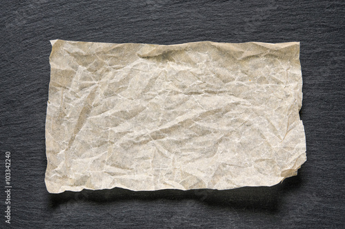Valokuva  Crumpled baking paper sheet on black slate stone with copy space for text as template food background