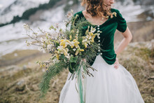 Bride Holding Wedding Bouquet Of Pine Branches And Greenery In R