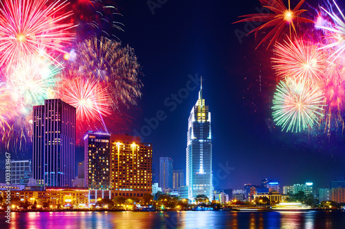 Celebration. Skyline with fireworks light up sky over business district in Ho Chi Minh City ( Saigon ), Vietnam. Beautiful night view cityscape, urban landscape. Holidays, celebrating New Year.