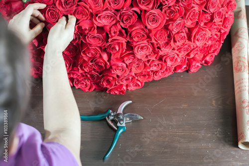 Photo  Florist woman prepares a big bouquet of red roses
