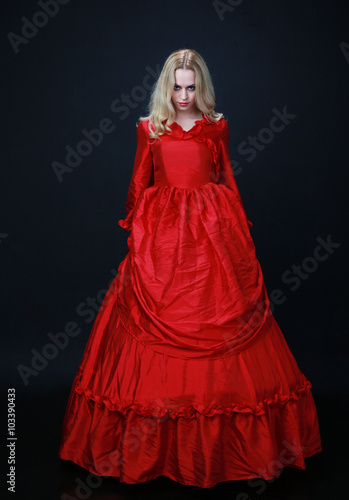 full length portrait of a beautiful blonde woman wearing a historical red silk, victorian era ball gown Canvas