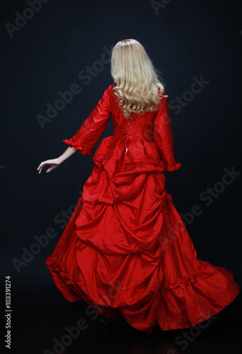 Foto  full length portrait of a beautiful blonde woman wearing a historical red silk, victorian era ball gown