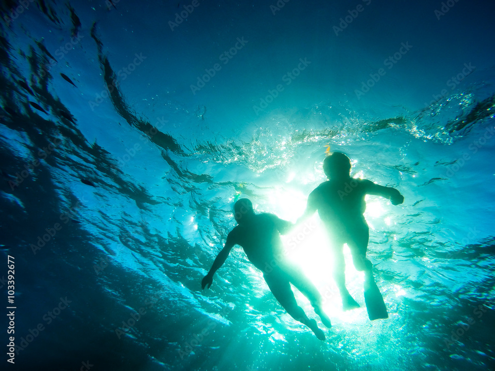 Fototapeta Silhouette of senior couple swimming together in tropical sea - Snorkeling tour in exotic scenarios - Concept of active elderly and fun around the world - Soft focus due to backlight and water density