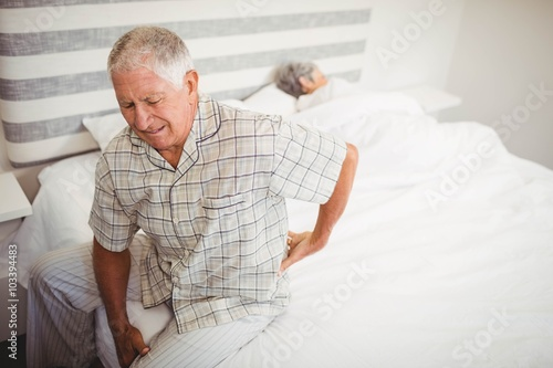 Valokuvatapetti Senior man suffering from backache sitting on bed
