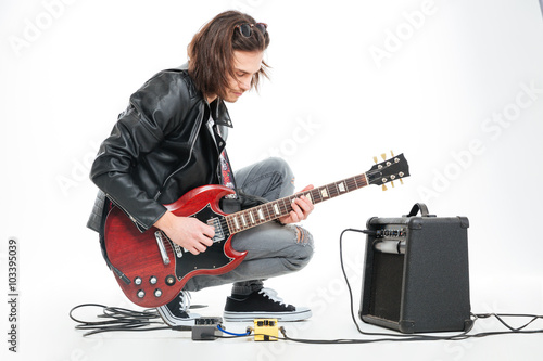 Cuadros en Lienzo Focused handsome young guitarist playing electric guitar with amplifier