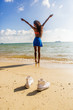 Beautiful teenage black girl in white sneakers on the sand of be