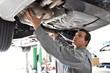 Mechaniker in einer Autowerkstatt kontrolliert Abgasanlage / Endschalldämpfer / Dieselpartikelfilter eines Fahrzeuges