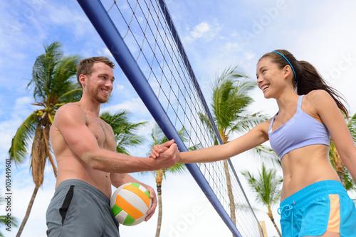Plakat Uścisk dłoni ludzie w plażowej siatkówki chwiania rękach po salwy piłki gry na lato plaży. Mężczyzna i kobieta model żyjący zdrowy aktywny styl życia robi sport na plaży.