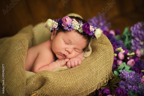 Beautiful newborn baby girl with a purple wreath sleeps in a wicker basket