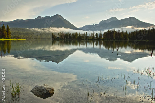 Foto auf Gartenposter Reflexion Sawtooth mountain peaks of Idaho reflected in the calm water of a lake