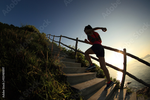 Fotografia  young fitness woman trail runner running up on mountain stairs