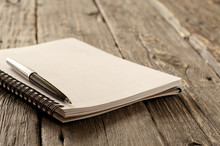 Open Notepad With Pen On Wooden Background