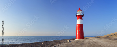Photo sur Toile Phare Red and white lighthouse and a clear blue sky