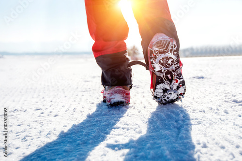 Tuinposter Alpinisme View of walking on snow with Snow shoes and Shoe spikes in winte