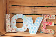 LOVE Written With  Colorful Wooden Letters Decorated In Decoupage Technique Posted On  Wooden Pallet