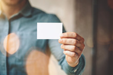 Man Wearing Blue Jeans Shirt And Showing Blank White Business Card. Blurred Background. Horizontal Mockup