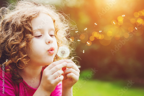 Staande foto Paardebloem Little curly girl blowing dandelion.