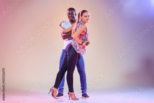 mata magnetyczna Young couple dances social Caribbean Salsa, studio shot