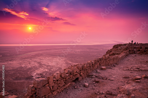 Photo Stands Candy pink Beautiful sunrise over Masada fortress. Ruins of King Herod's palace in Judaean Desert.