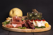 Various types of italian appetizers: ham, cheese, grissini, olives, fruits over black wooden background. Selective focus