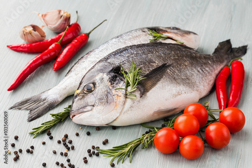 Fotobehang Vis Raw fresh dorado fish with vegetables and spices