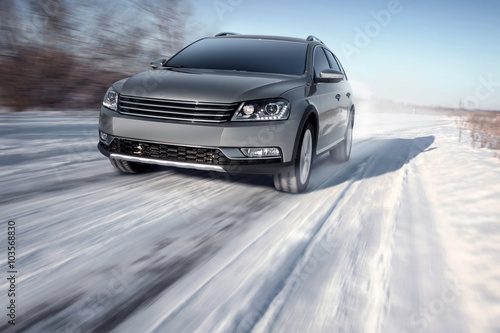 Fotografie, Obraz  Gray modern car drive speed on road at winter daytime