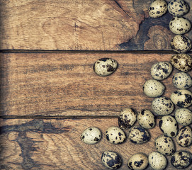 Quail eggs on wooden background. Retro style toned