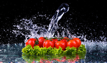 Panel Szklany Fresh tomato cherry and green fresh salad with water drop splash on dark background Macro drops of water fall on the red cherry tomatoes and make splash