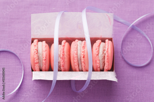 Pink macarons with buttercream filling in a box