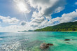 Empty Beach in Seychelles, Mahe island. Rocks and Palm trees in background with direct sunlight. Indian Ocean.