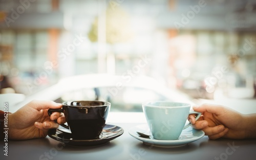 Friends holding cup of coffee
