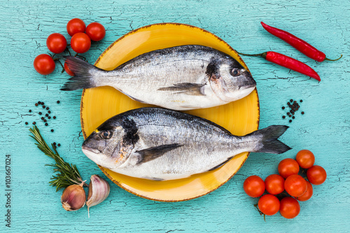 Foto op Plexiglas Vis Two fresh dorado fish on yellow plate and vegetables on blue table. Top view.