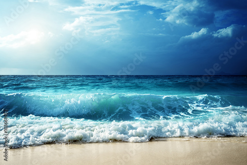 Foto op Aluminium Zee zonsondergang waves at Seychelles beach